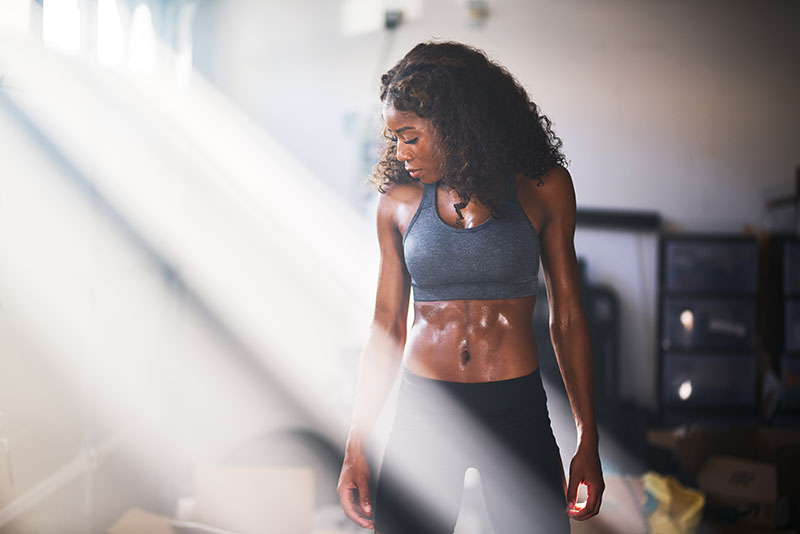 Woman in workout gear shows of tightened and toned body from Emsculpt