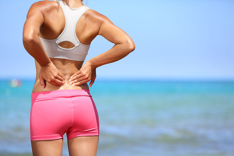 Holding aching back from pain | SF Bay Cosmetic Body Sculpting