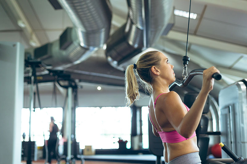 Woman who is considering Emsculpt working out at a gym